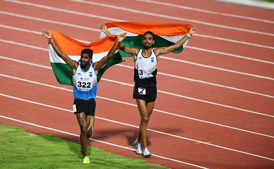 G Lakshmanan (L) and Gopi Thonakal celebrate after winning gold and silver respectively in the men's 10,000m. AFP
