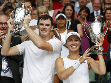 Jamie Murray and Martina Hingis hold their mixed doubles winners trophies. AFP