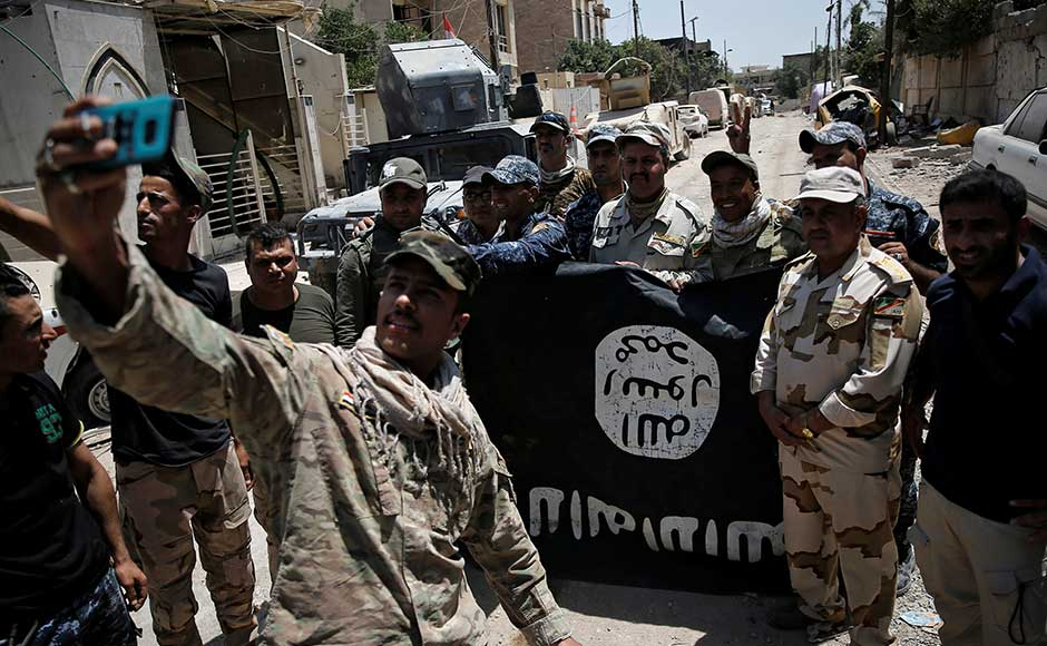 Members of Iraqi Army's ninth armoured division click selfies with an Islamic State flag. The special forces have recaptured more of Mosul's historic heart, as they press the final stages of an assault to drive the Islamic State group from Iraq's second largest city, the military said on Sunday. Reuters