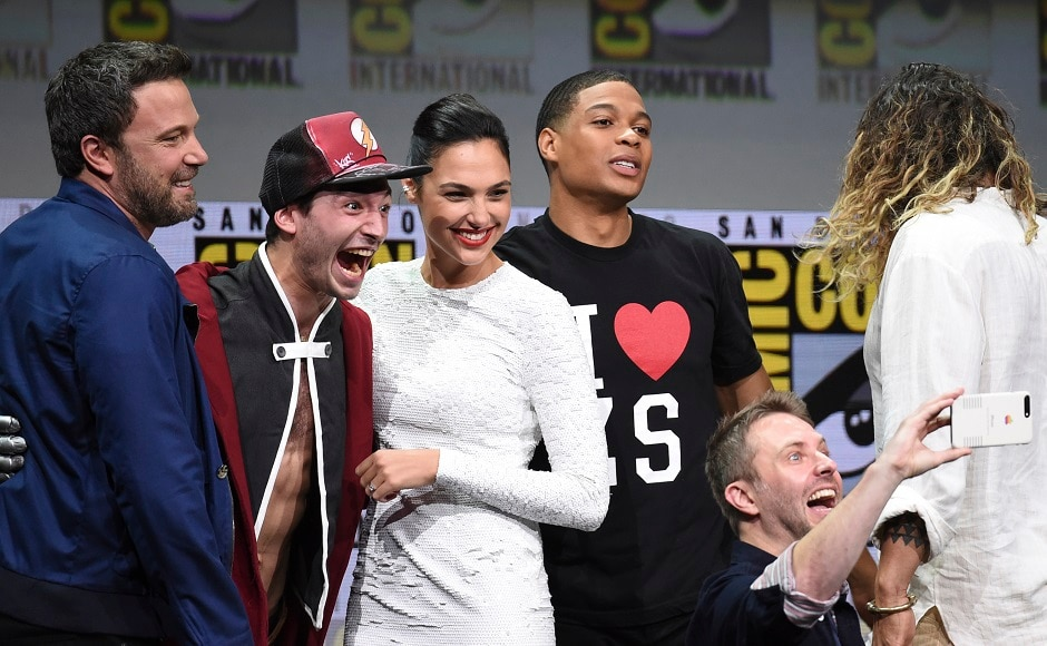 Moderator Chris Hardwick, foreground right, takes a selfie with from left, Ben Affleck, Ezra Miller, Gal Gadot, and Ray Fisher at the Warner Bros. Justice League panel on day three. Photo by AP