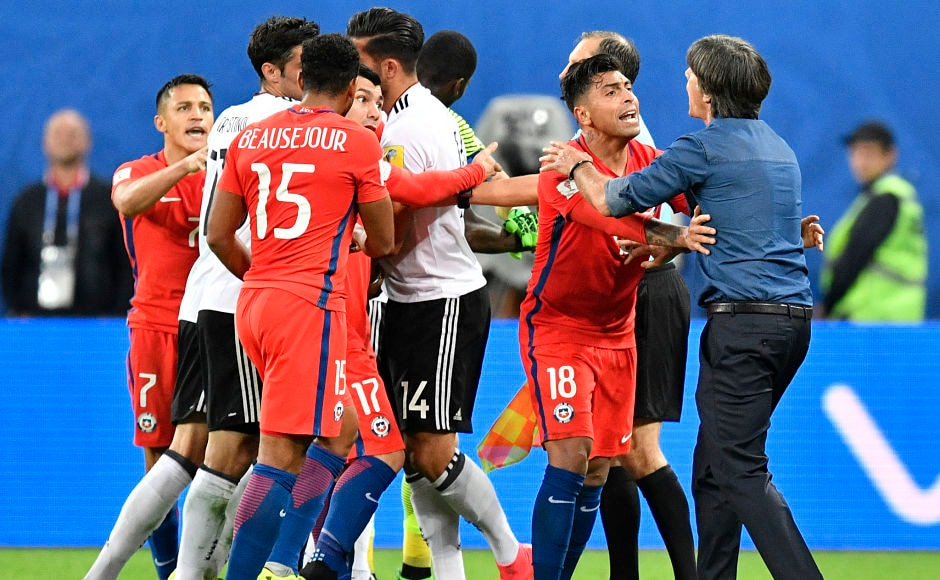 As the game progressed, the Chilean tempers started to fray. Germany coach Joachim Loew(R) tries to mediate an argument between Emre Can and Chile players. AP