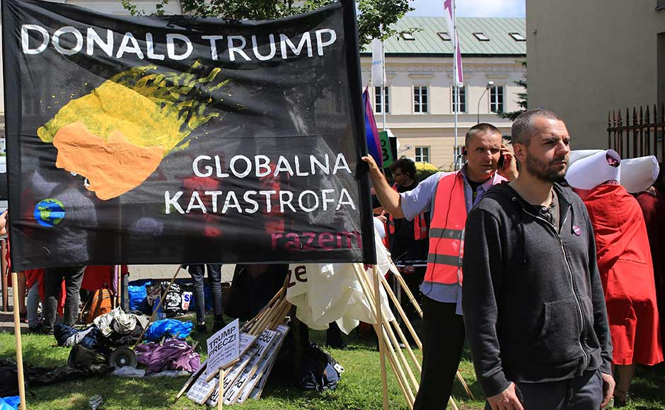 "Small scale protests were held during Trump's visit. In this image, a man stands in front of a banner against the US president ahead of his public speech in Warsaw. The banner reads in Polish, ""global catastrophe"". Reuters"