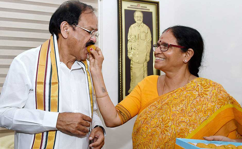 The government also hopes that Naidu's vast parliamentary experience will help in the smooth conduct of Rajya Sabha proceedings. <br />In this image, Naidu is offered sweets by his wife Usha at his residence. PTI