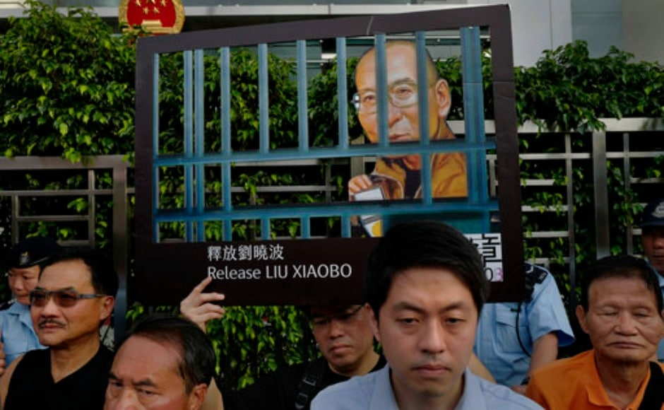 "Protesters display portrait of jailed Chinese Nobel Peace laureate Liu Xiaobo during a demonstration outside the Chinese liaison office in Hong Kong on Monday. The hospital treating Xiaobo said his condition is now critical and doctors are in ""active rescue"" mode for China's best-known political prisoner. AP"