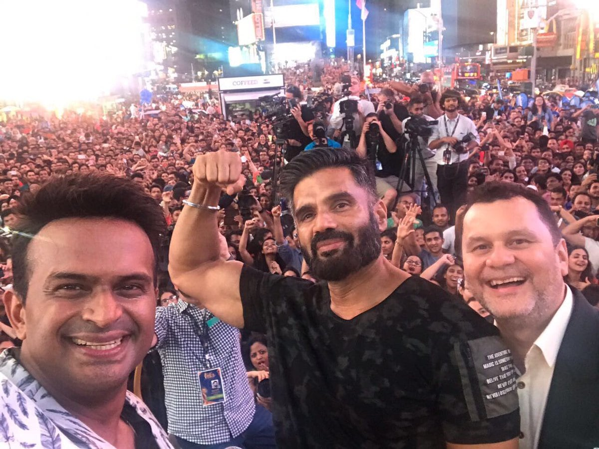 Suniel Shetty poses for a photo with his fans going crazy in the back. Image from Twitter/IIFA.
