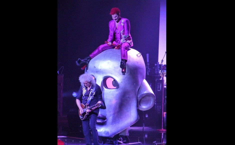 Adam Lambert sits atop a stage prop while Queen's Brian May plays the guitar. Image from Twitter