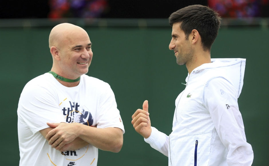 Novak Djokovic speaks with his coach former Wimbledon champion Andre Agassi on day two of the Wimbledon Tennis Championships in London.<br />AP