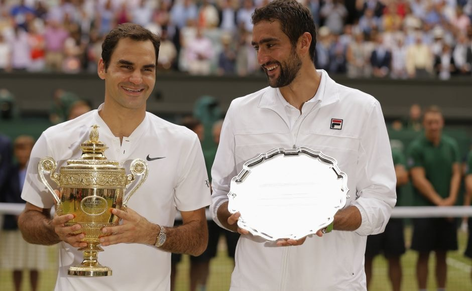 Federer holds the winners trophy alongside Cilic, with the runners up plate. AP
