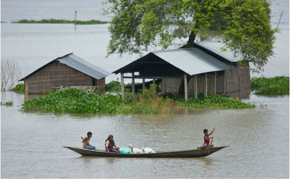 A boy rows a boat to cross flood waters at Burgaon, 80 kilometres east of Guwahati in Assam on Thursday. AP