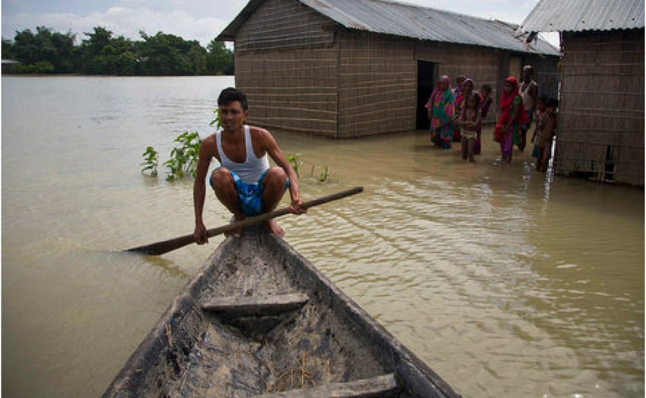A man paddles a boat near submerged houses at Burgaon, 80 kilometres east of Guwahati in Assam. AP