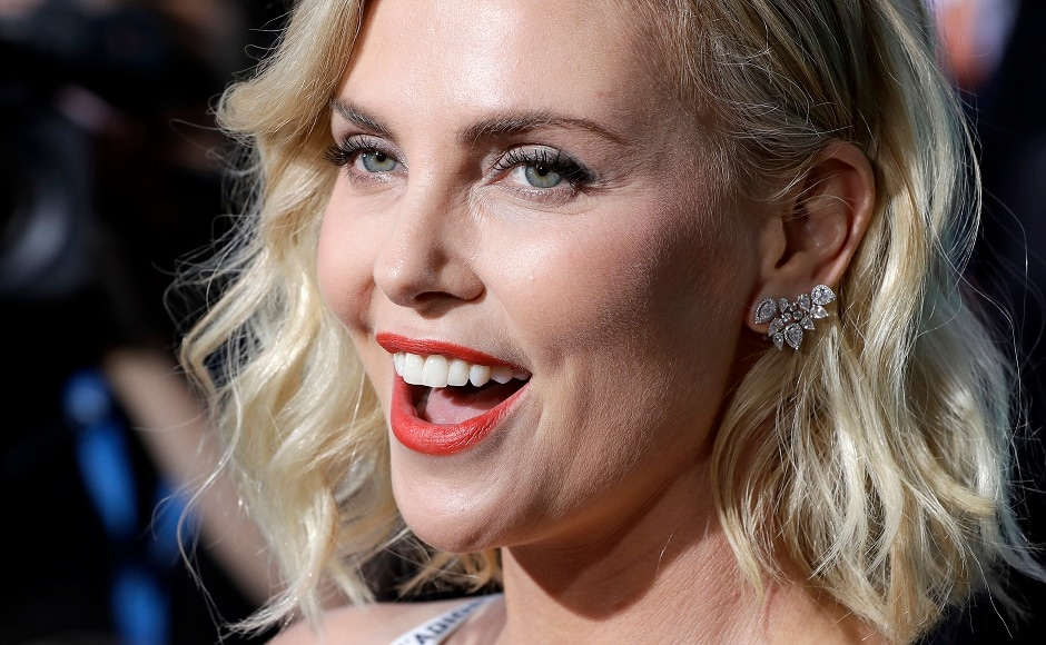 Actress Charlize Theron talks to journalists as she arrives for the world premiere of the movie Atomic Blonde in Berlin, Germany, Monday, 17 July, 2017. Image via AP/Michael Sohn