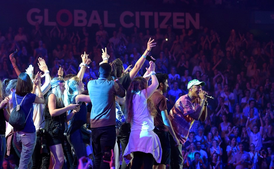 Singer Pharrell Williams, right, performs at the Global Citizen Festival concert on the eve of the G-20 summit in Hamburg, northern Germany, Thursday, July 6, 2017. The leaders of the group of 20 meet July 7 and 8. (AP Photo/Jens Meyer)