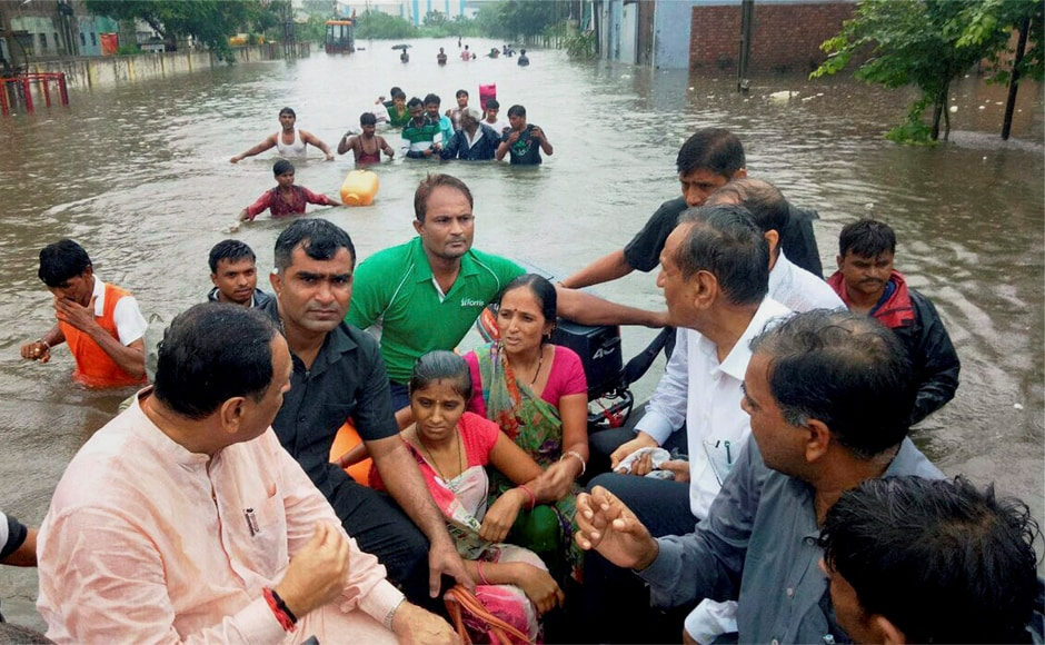Gujarat chief minister Vijay Rupani with the flood affected people as many areas remain inundated by waters after heavy rains in Ahmedabad on Thursday. PTI