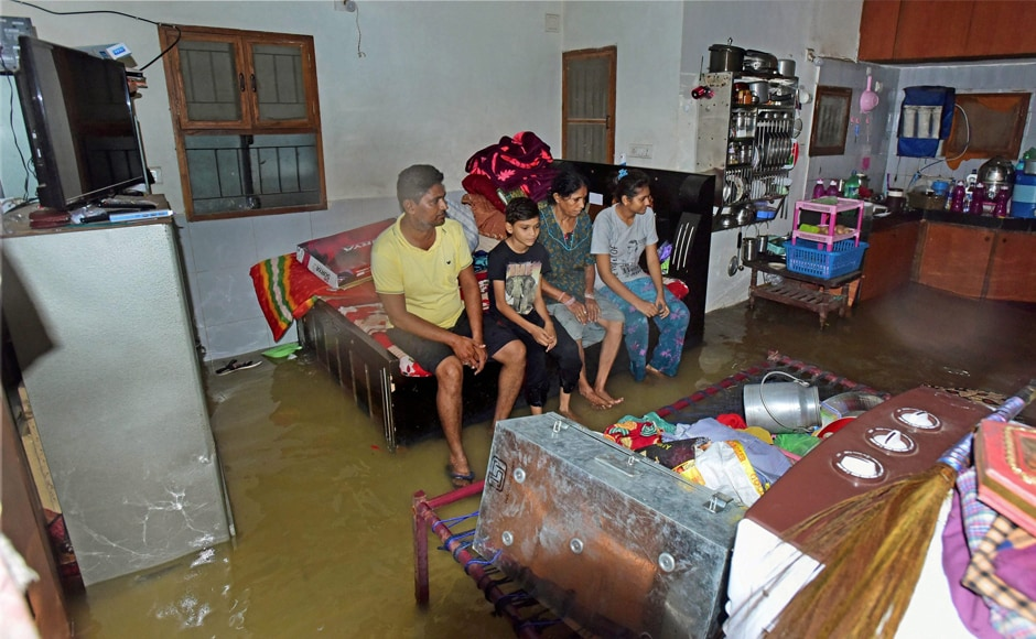 A family in a waterlogged house after heavy rainfall in Vejalpur in Ahmedabad on Thursday. Portions of at least 20 buildings collapsed due to heavy rains and waterlogging, officials said. PTI