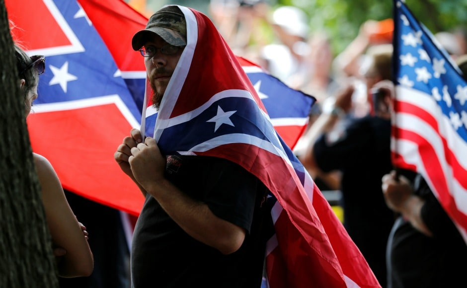 "Dozens of marchers — some carrying Confederate flags, a handful in the distinctive white hood worn by Klan members — paraded past hundreds of people shouting ""Racists go home!"" and other chants. The two groups were separated by a metal barricade and a phalanx of armed police. Reuters"
