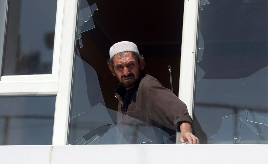 A man removes broken glasses from a window at the site of the suicide attack in Kabul. Most of the casualties were civilians, including women and children, but the dead also included Afghan security guards. AP