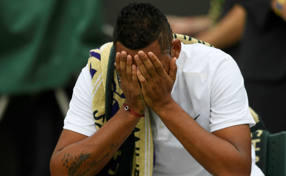 Dejected Nick Kyrgois buries his face into his hands as he is knocked out of the first round of Wimbledon. The 20th seed was losing 3-6, 4-6 to Pierre-Hugues Herbert after which he was forced to retire due to hip injury. Reuters
