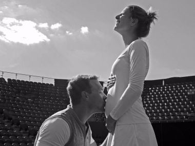 Mandy Minella's husband and coach Tim Sommer kneeling in front of her, kissing her stomach. Twitter/@mandyminella