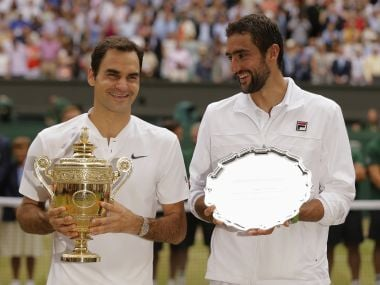 Roger Federer, left, holds the winners trophy alongside Marin Cilic with the runners up plate. AP