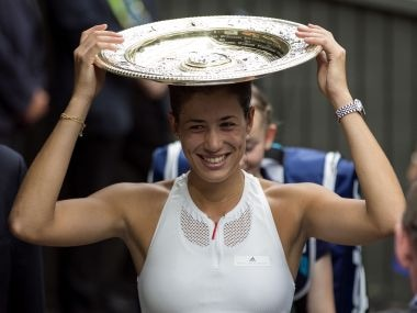 Spain's Garbine Muguruza holds the trophy as she leaves the court after defeating Venus Williams of the United States in the Women's Singles final match on day twelve at the Wimbledon Tennis Championships in London Saturday, July 15, 2017. (Steven Paston/PA via AP)