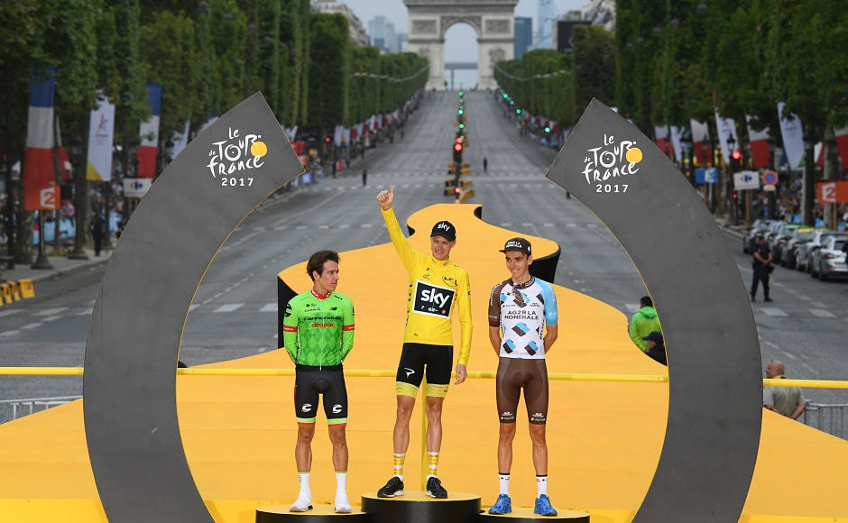 Tour de France winner Chris Froome, wearing the overall leader's yellow jersey, second place Rigoberto Uran of Colombia(L) and third place Romain Bardet of France (R) celebrate on the podium. AP