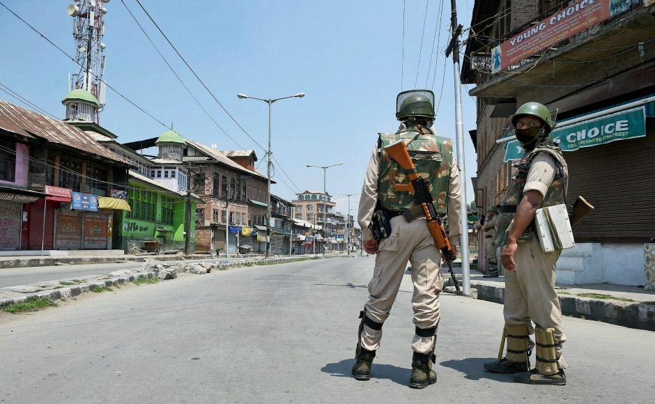 Two security personnel stand guard during a restriction in Anantnag. PTI