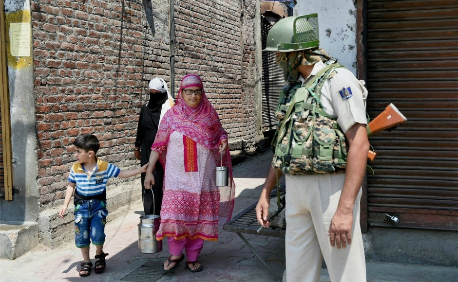 A woman with her child walks past a security personnel during a strike in Srinagar on Sunday. PTI