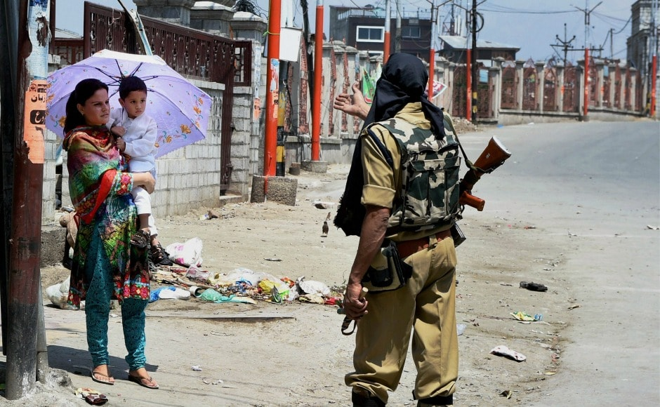 A security personnel asks a woman to take another route since authorities imposed a restriction in certain parts of Srinagar. PTI