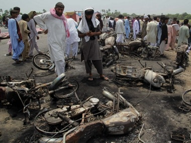 Local residents examine burnt motorcycles at the site of the tanker fire. AP