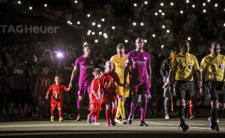 Manchester City and Real Madrid take to the field during the opening ceremony at the Los Angeles Memorial Coliseum. AP