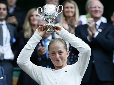 Jelena Ostapenko of Latvia holds the winners trophy after defeating Kristina Schmiedlova of Slovakia in their girl's singles final tennis match at the Wimbledon Tennis Championships, in London July 6, 2014. REUTERS/Stefan Wermuth (BRITAIN - Tags: SPORT TENNIS) - RTR3XDFQ