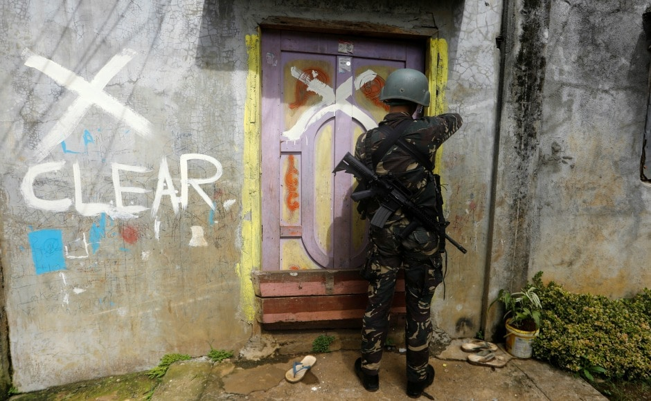 A member of the Philippine National Police closes a door after marking a house as clear while government troops continue their assault against insurgents from the Maute group in Marawi city. According to government sources some 1,500 homes still need to be cleared of explosives and soldiers are able to clear only 70 to 100 homes a day. Reuters