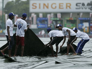 Ground workers pull the covers to cover the ground as the match was stopped due to rain, on the first day of third and final test cricket match between India and Sri Lanka in Colombo August 28, 2015. REUTERS/Dinuka Liyanawatte - RTX1PZJW