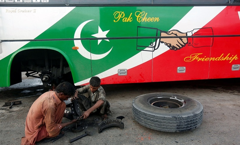 Workers sit on ground as they repair a bus' brake shoes, displaying the Pak-China friendship sign, along a road in Karachi, Pakistan May 30, 2017. REUTERS/Akhtar Soomro - RTX38940