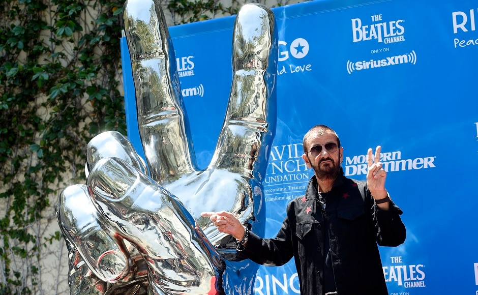 Ringo Starr mimics a peace sign statue during a 77th birthday celebration for the former Beatle at Capitol Records on Friday, July 7, 2017, in Los Angeles. Photo by AP