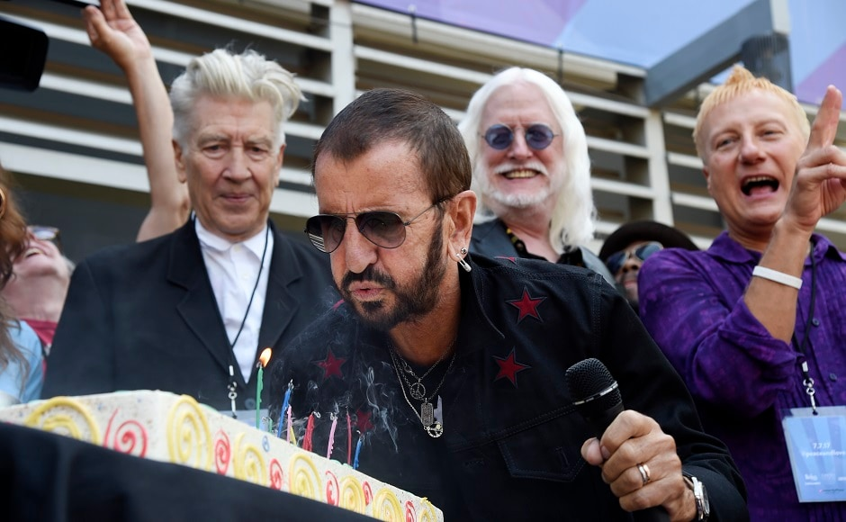 Ringo Starr blows out candles on his birthday cake in front of guests including filmmaker David Lynch, left, and musician Edgar Winter, second from right. Photo by AP