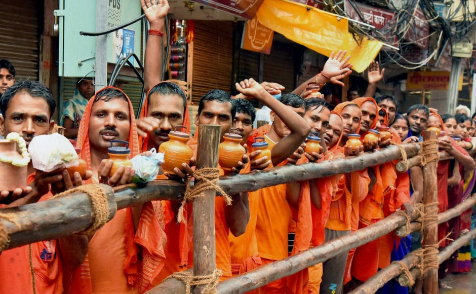Devotees stand in a queue to offer water to Lord Shiva's idol at Kashi Vishwanath temple on the occasion of first Monday of Sawan, the holiest month for Hindus, in Varanasi. PTI