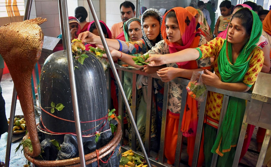 Women observe rituals of Sawan at Gurugram on Monday. PTI