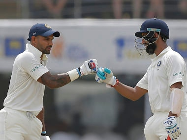 India's Cheteshwar Pujara, right, and Shikhar Dhawan cheer at each other during the first day's play of the first test cricket match between India and Sri Lanka in Galle, Sri Lanka, Wednesday, July 26, 2017. (AP Photo/Eranga Jayawardena)
