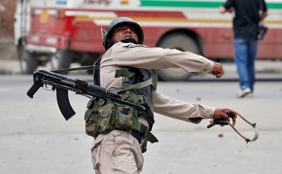A police officer throws a rock at stone pelters during disturbances in Srinagar. Slender employment prospects prompt many residents of the region to join the police force. Reuters