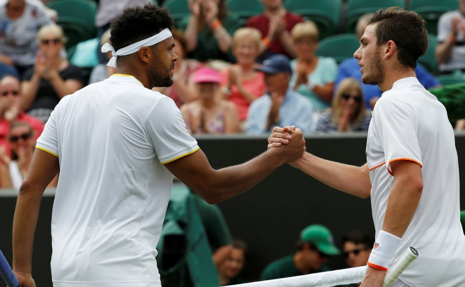 Wildcard entry Cameron Norrie congratulates Frenchman Jo-Wilfried Tsonga, who beat him 6-3, 6-2, 6-2 and advances into the second round of Wimbledon. Reuters