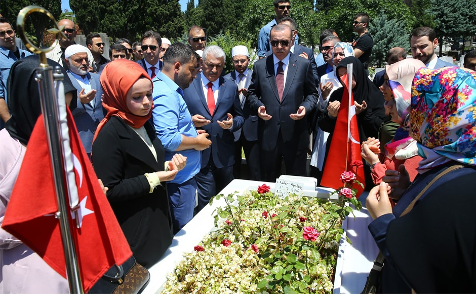 "Erdogan (centre) and Turkey's prime minister Binali Yildirim, (centre left) attend a prayer by the grave of a victim of the failed coup attempt, in Istanbul on Tuesday. Erdogan once described the coup as a ""gift from God"" that had allowed the government to purge the military and public institutions of the 'Gulenists' who once were allied with his Islamic-rooted Justice and Development Party. AP"