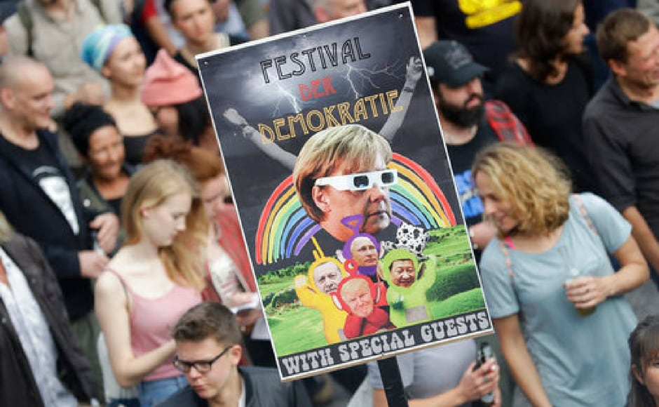A demonstrator holds a poster with a altered image of German chancellor Angela Merkel during a dancing protest against the G20 summit in Hamburg. AP