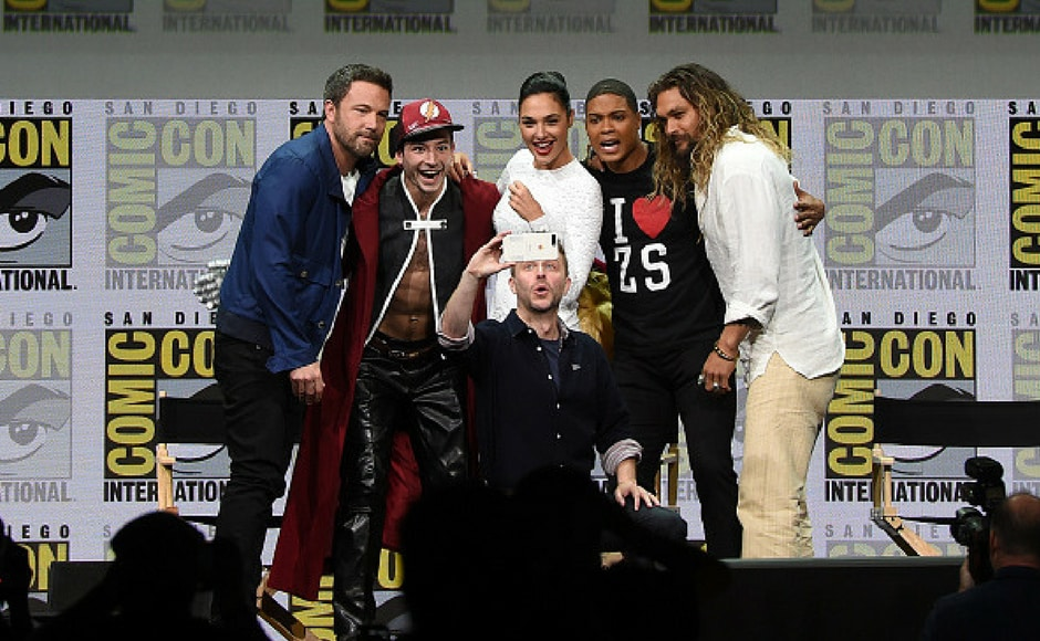 (L-R) Actors Ben Affleck, Ezra Miller, Gal Gadot, Ray Fisher, and Jason Momoa from Justice League attend the Warner Bros. Pictures Presentation while moderator Chris Hardwick takes a selfie during Comic-Con International 2017. (Getty Images)