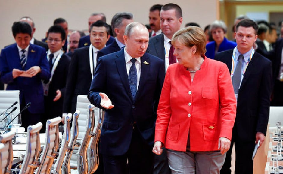 Merkel talks with Russia's president Vladimir Putin at the start of the first working session of the G20 meeting. AP
