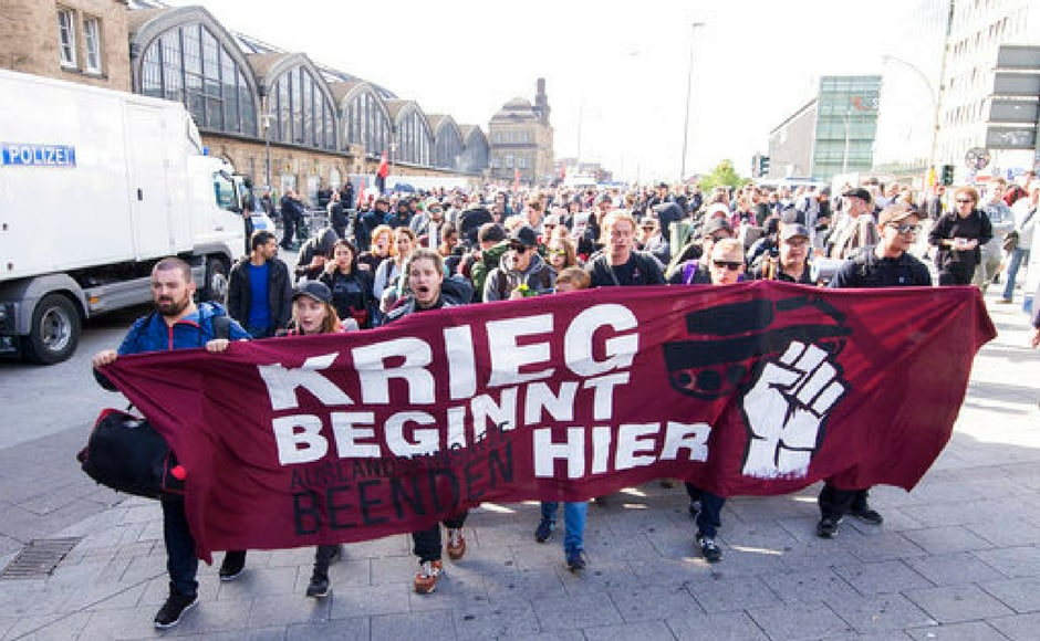 "Activists carry a banner reading ""The war starts here"" as they march to their camp during the G20 summit. Reuters"