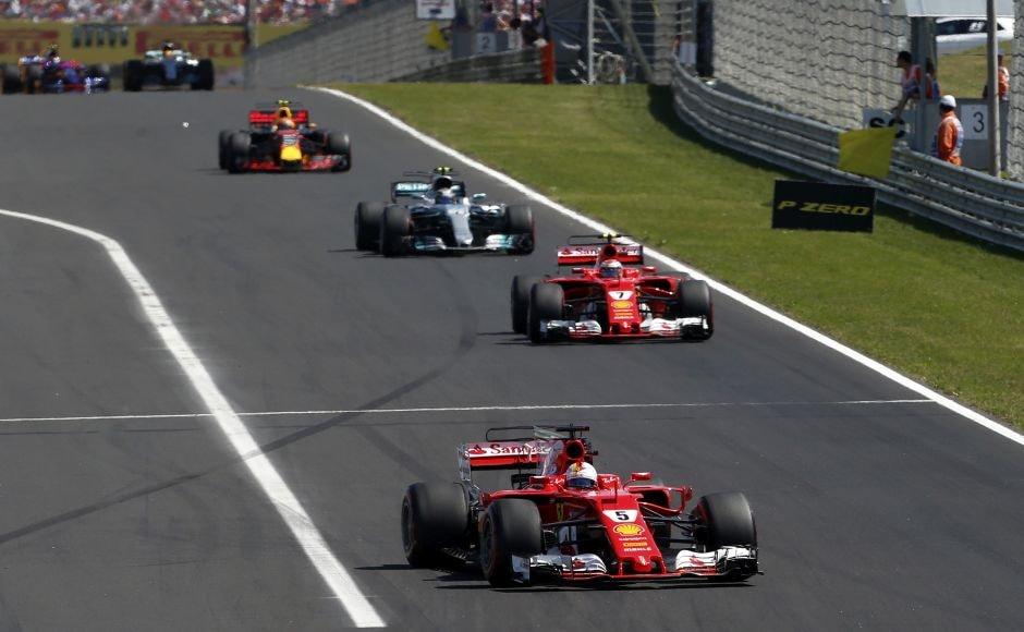 Vettel crucially held off teammate Kimi Raikkonen on the long straight into Turn 1. AP