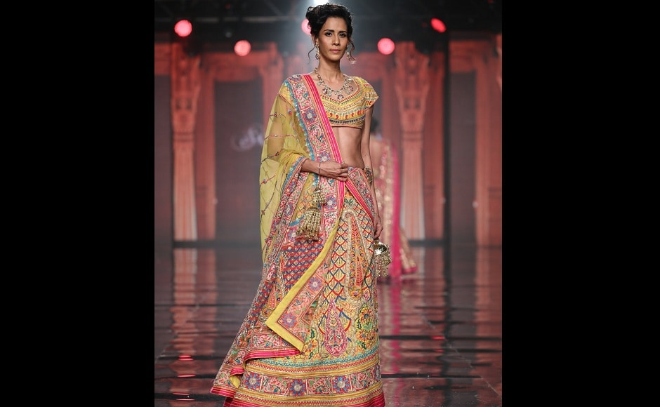 A mdoel walks the ramp wearing a lehenga which looks like a riot of colours.
