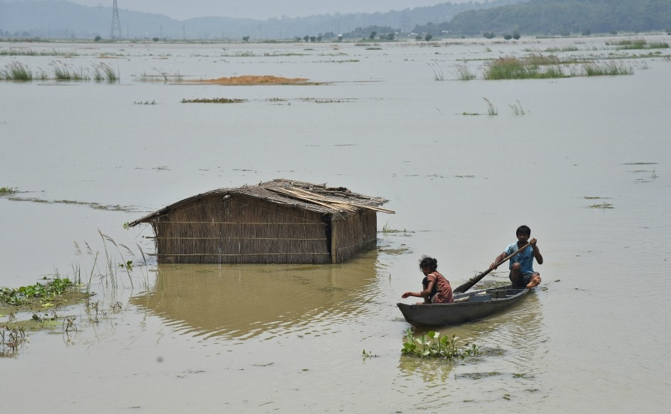 A boy rows a boat past a submerged hut in a flooded field at Mayong village in Morigaon district of Assam. Close to 12 lakh people in 24 districts of Assam continued to reel under floods as the death toll reached 60 in the state on Saturday. Reuters
