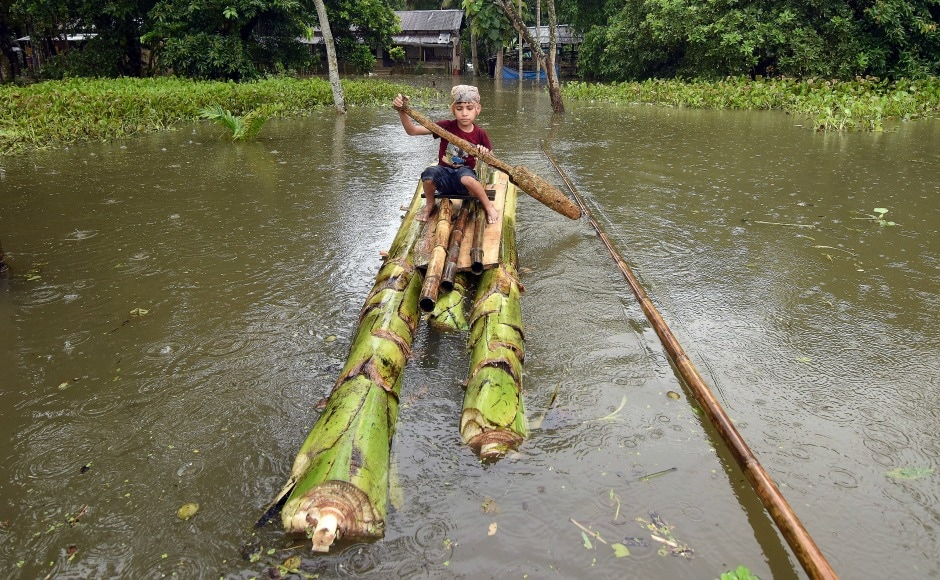 A boy rows a makeshift raft outside his submerged house in the flood-affected Kuthori village near Kaziranga National Park in Nagaon district of Assam. Over 66,516 hectares of agricultural land continue to be affected by floods, a report said. Reuters